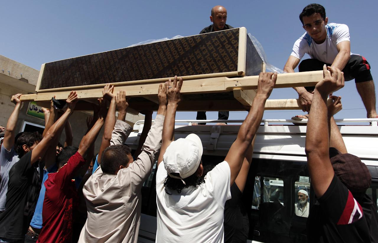 Mourners unload the coffin of an Iraqi woman who was killed along with her husband in a car bomb attack during their honeymoon, her family said, during the funeral in the Shiite holy city of Najaf, 100 miles (160 kilometers) south of Baghdad, Iraq, Sunday, Aug. 11, 2013. A wave of car bombings targeting those celebrating the end of Ramadan across Iraq killed scores of people Saturday, a bloody reminder of the inability of Iraqi authorities to stop violence threatening to spiral out of control. (AP Photo/ Haider Hamdani)