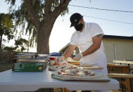 Chef Jose Hernandez preps several pizzas at his makeshift backyard pizza kitchen in Scottsdale, Ariz. on April 3, 2021. Hernandez and his wife Ruby Salgado spend their weekends making pizzas in a backyard oven they built. Some nights, they churn out as many as 30 pies with toppings like fennel sausage, fresh mozzarella and carne asada. (AP Photo/Ross D. Franklin)