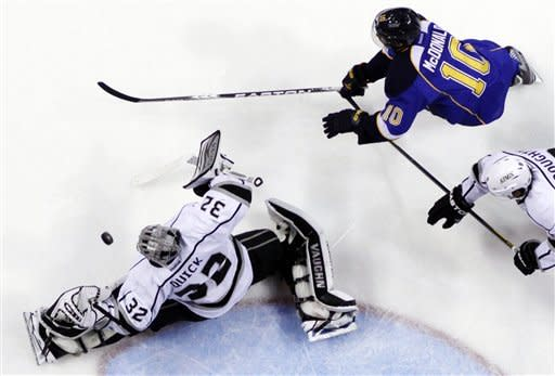 Los Angeles Kings goalie Jonathan Quick (32) deflects a shot as St. Louis Blues' Andy McDonald gives chase during the second period of Game 1 in a second-round NHL Stanley Cup hockey playoff series, Saturday, April 28, 2012, in St. Louis. (AP Photo/Jeff Roberson)