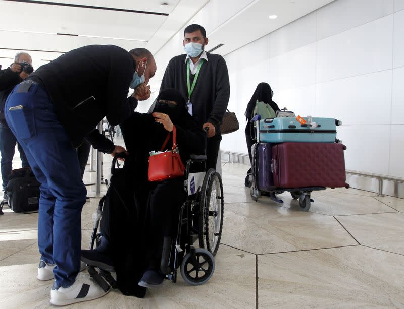 Man kisses the hand of his relative who arrived from Doha, at King Khalid International Airport in Riyadh