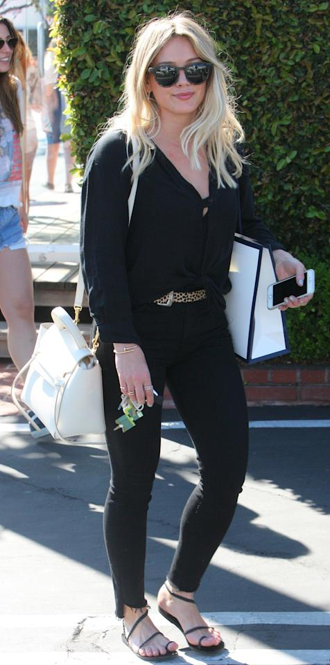 """<p>Duff stepped out in an all-black ensemble featuring a knotted button-down top, black jeans held up by a leopard-print belt (get a similar belt from <a rel=""""nofollow"""" href=""""https://click.linksynergy.com/fs-bin/click?id=93xLBvPhAeE&subid=0&offerid=465536.1&type=10&tmpid=2425&RD_PARM1=http%3A%2F%2Fwww1.bloomingdales.com%2Fshop%2Fproduct%2Fkate-spade-new-york-leopard-calf-hair-spade-buckle-belt%3FID%3D1821211%2526CategoryID%3D3631%2526LinkType%3D&u1=ISHilaryDuffStreetStyle3.13JA"""">Bloomingdale's</a>), a white tote, and black sandals. </p>"""