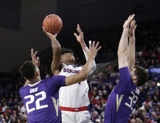 Gonzaga forward Rui Hachimura, center, shoots between Washington forward Dominic Green (22) and forward Sam Timmins (33) during the first half of an NCAA college basketball game in Spokane, Wash., Wednesday, Dec. 5, 2018. (AP Photo/Young Kwak)