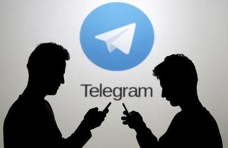 Two men pose with smartphones in front of a screen showing the Telegram logo in this picture illustration taken in Zenica