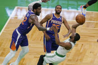 Boston Celtics guard Kemba Walker shoots and scores while falling backward, next to the defense of Phoenix Suns center Deandre Ayton (22) and forward Mikal Bridges (25) in the second half of an NBA basketball game Thursday, April 22, 2021, in Boston. (AP Photo/Elise Amendola)