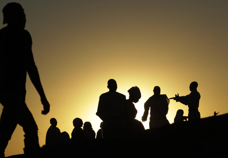 Zimbabweans sit and pray on top of a large rock on the outskirts of Harare, Zimbabwe, Sunday, Sept. 8, 2019. Former president Robert Mugabe, who enjoyed strong backing from Zimbabwe's people after taking over in 1980 but whose support waned following decades of repression, economic mismanagement and allegations of election-rigging, is expected to be buried next Sunday, state media reported. (AP Photo/Themba Hadebe)