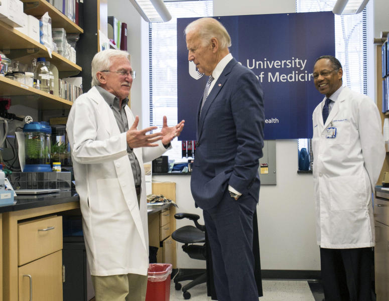 FILE - In this Feb. 10, 2016 file photo, Vice President Joe Biden speaks with Nobel Laureate Dr. Paul Modrich, left, as Dr. A. Eugene Washington, Chancellor for Health Affairs at Duke University, right listens in a laboratory at Duke University School of Medicine in Durham, N.C. Biden's defining venture since leaving the Obama White House is the Biden Cancer Initiative, a nonprofit aimed at speeding a cancer cure in memory of his son.  (AP Photo/Ben McKeown)