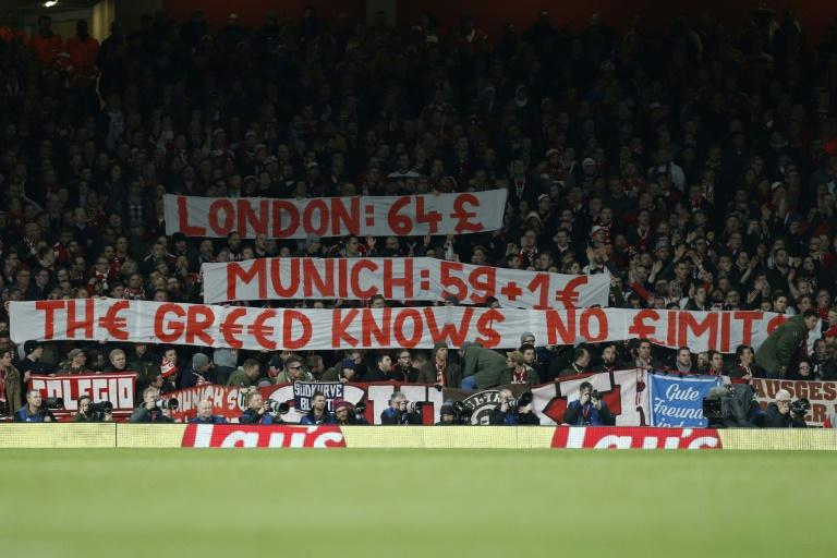 Bayern Munich fans raise banners to complain about the cost of match day tickets during the Champions League last 16 second leg against Arsenal at The Emirates Stadium in London on March 7, 2017