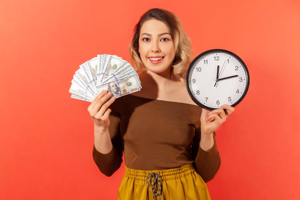 Happy woman holding dollar bills in one hand and a clock in the other.