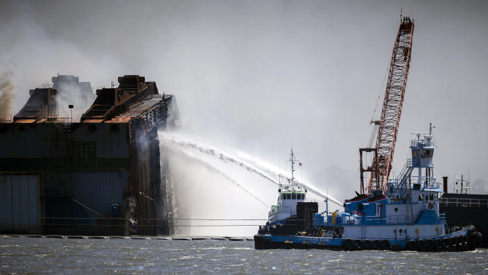 Firefighters working off two tug boats hose down the remains of the overturned cargo ship Golden Ray, Friday, May 14, 2021, Brunswick, Ga. The Golden Ray had roughly 4,200 vehicles in its cargo decks when it capsized off St. Simons Island south of Savannah on Sept. 8, 2019. (AP Photo/Stephen B. Morton)
