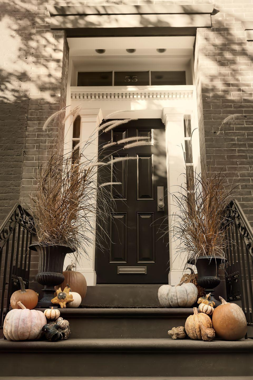"""<p>Don't fret if you prefer to avoid over-the-top Halloween decorations that detract from your exterior's aesthetic. Complement your home's black and white entrance by grouping pumpkins in different sizes right on your front steps. </p><p><a class=""""link rapid-noclick-resp"""" href=""""https://go.redirectingat.com?id=74968X1596630&url=https%3A%2F%2Fwww.etsy.com%2Flisting%2F627434602%2F25-fall-winter-wedding-decor-mini-real&sref=https%3A%2F%2Fwww.goodhousekeeping.com%2Fholidays%2Fhalloween-ideas%2Fg32948621%2Fhalloween-door-decorations%2F"""" rel=""""nofollow noopener"""" target=""""_blank"""" data-ylk=""""slk:SHOP WHITE PUMPKINS"""">SHOP WHITE PUMPKINS</a></p>"""