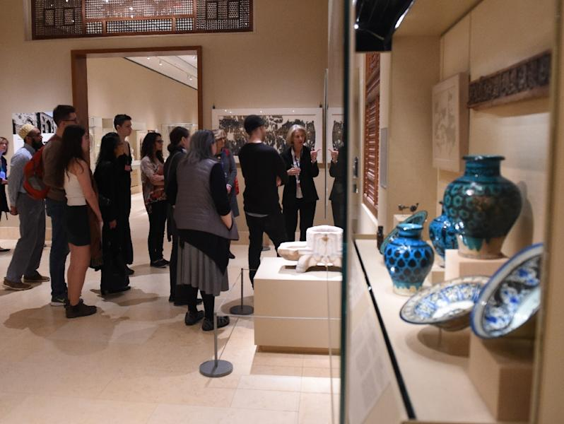 Curators at the Metropolitan Museum of Art talk to visitors about works created in the lands that are now Iraq, Syria, Iran and Yemen, four of the seven countries affected by the recent travel ban (AFP Photo/TIMOTHY A. CLARY)