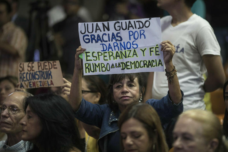 "A supporter of opposition National Assembly President Juan Guaido holds a sign with a message that reads in Spanish: ""Thank you Juan Guaido for giving us hope and faith. On our way to democracy"", during a conference on economic plans for reviving the country at Venezuelan Central University, in Caracas, Venezuela, Thursday, Jan. 31, 2019. An independent U.N. human rights monitor says economic sanctions are compounding a ""grave crisis"" in Venezuela. (AP Photo/Rodrigo Abd)"