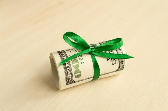 A roll of $100 bills tied with a green ribbon bow.