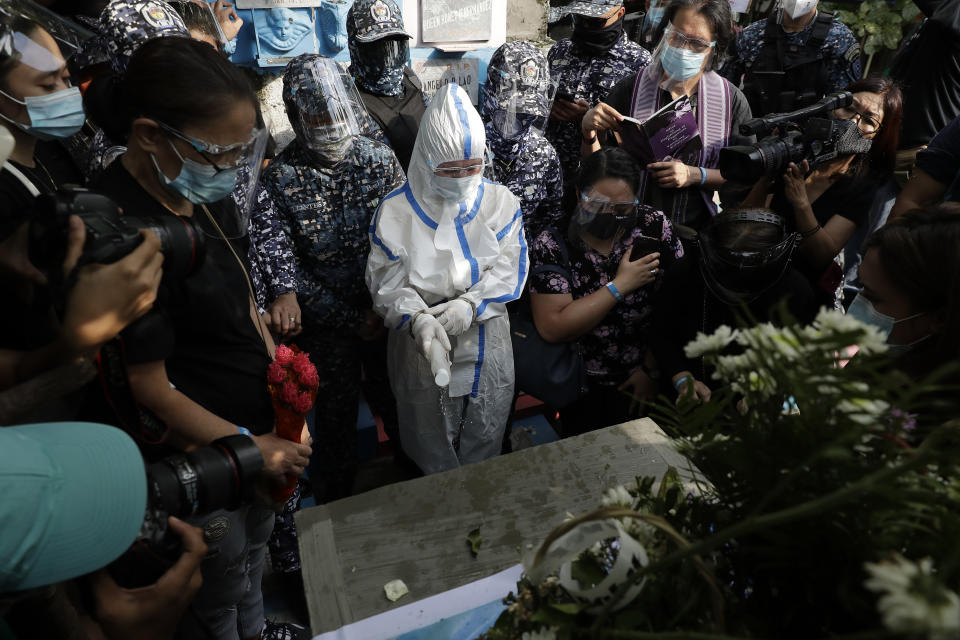 Detained left-wing activist Reina Mae Nasino in handcuffs and wearing a protective suit to prevent the spread of the coronavirus sprinkles holy water on the coffin of her three-month-old firstborn named River during funeral rites at Manila's North Cemetery, Philippines on Friday Oct. 16, 2020. Left-wing groups on Friday decried the treatment as brutal of a detained activist, who was allowed by a Manila court to attend her baby's burial but was restrained with handcuffs, a sweltering protective suit and swarms of armed escorts as she quietly wept. (AP Photo/Aaron Favila)