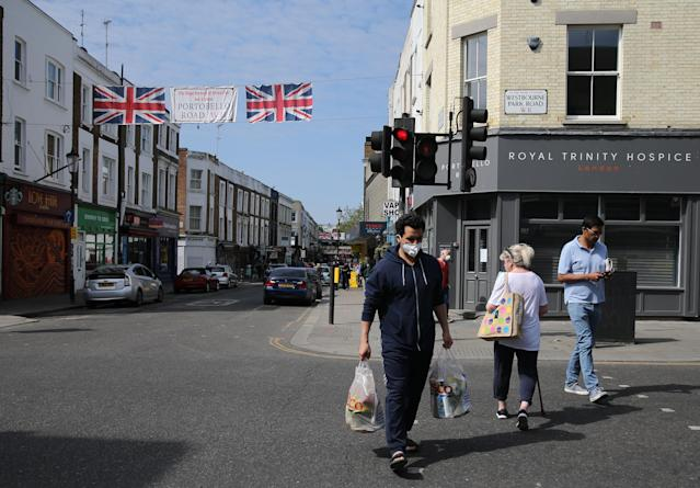 A man wearing a face mask shops in Portobello Road, west London, as the UK continues in lockdown. (PA)