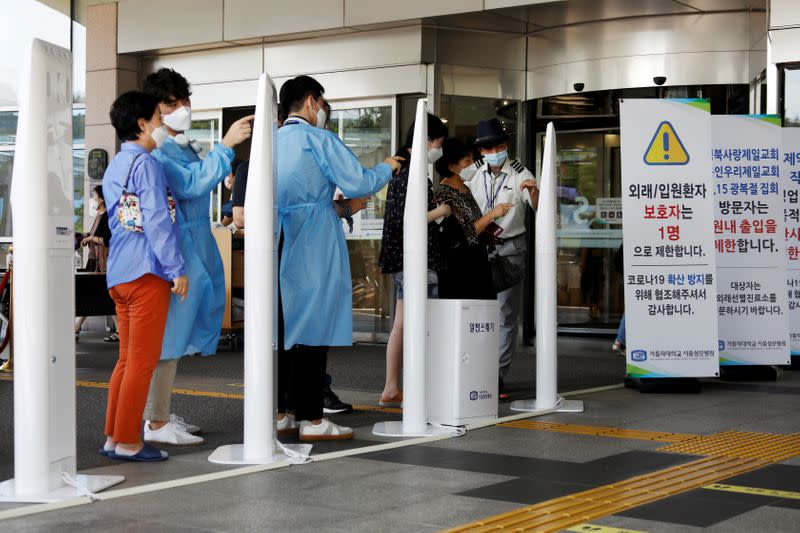 FILE PHOTO: Visitors wearing masks to avoid the spread of the coronavirus disease (COVID-19) fill out a form which is mandatory to get into a hospital in Seoul