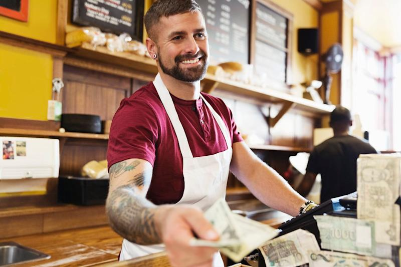 Cafe worker takes payment at counter. Source: Getty