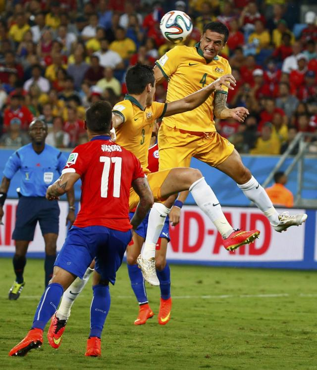 Australia's Tim Cahill (R) heads the ball during their 2014 World Cup Group B soccer match against Chile at the Pantanal arena in Cuiaba June 13, 2014. REUTERS/Paul Hanna (BRAZIL - Tags: SOCCER SPORT WORLD CUP)