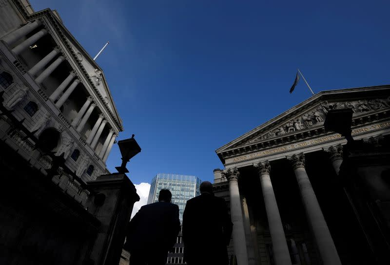 FILE PHOTO: Workers emerge from Bank underground station with the Bank of England and Royal Exchange building seen in the City of London financial district, London, Britain