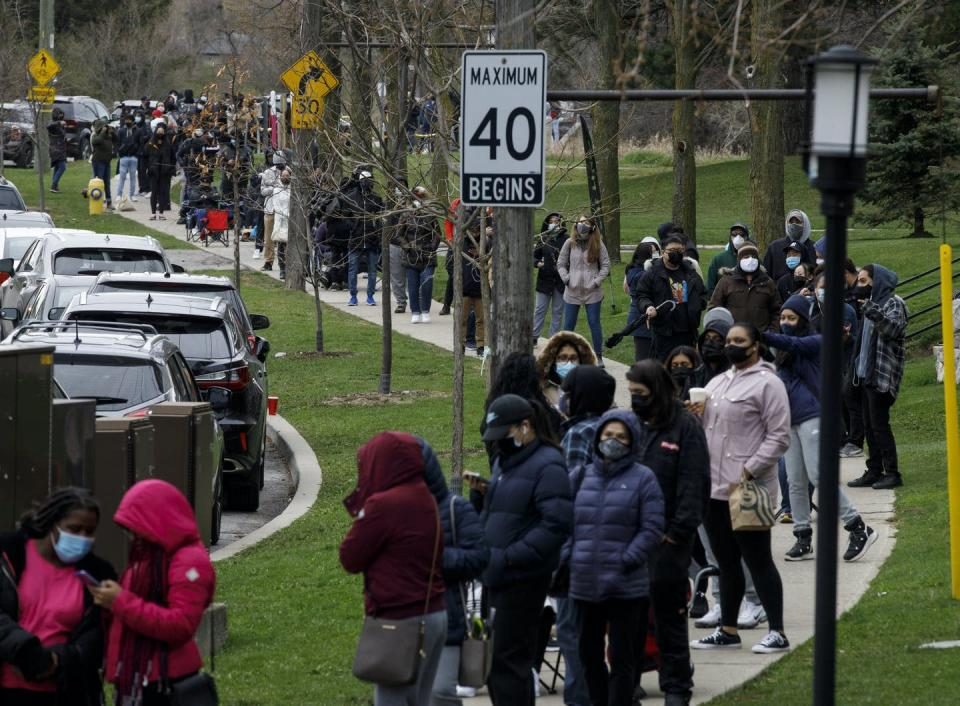 """<span class=""""caption"""">Hundreds of residents of Toronto's M3N postal code, a hotspot for COVID-19 infections, line up at a pop-up vaccine clinic on In April 2021. </span> <span class=""""attribution""""><span class=""""source"""">THE CANADIAN PRESS/Cole Burston </span></span>"""