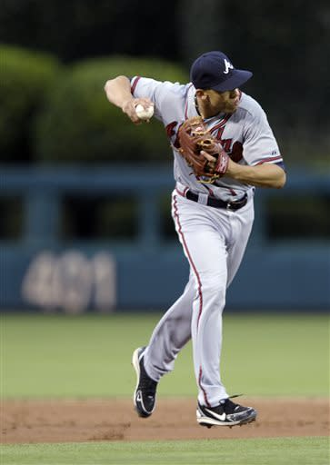 Atlanta Braves' Andrelton Simmons fields a ball hit by Philadelphia Phillies' Kyle Kendrick and throws him out in the third inning of a baseball game on Saturday, July 6, 2013, in Philadelphia. (AP Photo/Michael Perez)