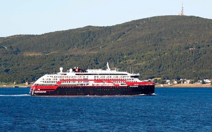 The expedition cruise ship Roald Amundsen leaves harbour in Tromso's city center and is heading towards Breivika harbour north of the city, on August 2, 2020. - At least 36 crew members and three passengers onboard the ship owned by the Norwegian company Hurtigruten, a specialist in expedition cruises, have so far tested positive for the new coronavirus.