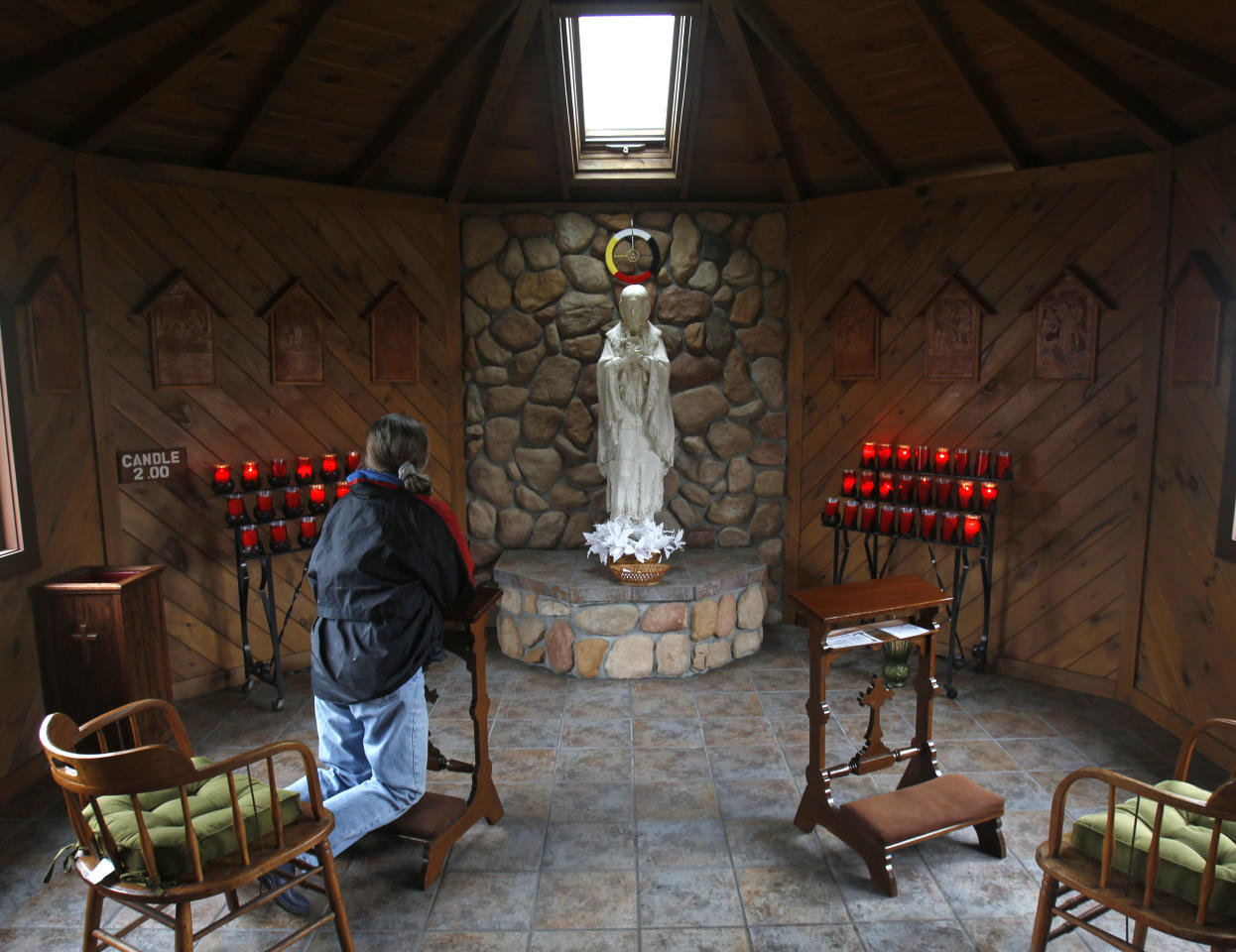 in a Wednesday, Dec. 21, 2011 photo, Mary Ann Delany of Amsterdam, N.Y., says a prayer in front of a statue of the the Blessed Kateri Tekakwitha at the National Kateri Shrine and Indian Museum in Fonda, N.Y. Tekakwitha, who will be canonized next year, was a Native American baptized in 1676 in the Mohawk Valley. She fled to a mission in Canada after being scorned and threatened in her home village near what is now the village of Fonda. (AP Photo/Mike Groll)