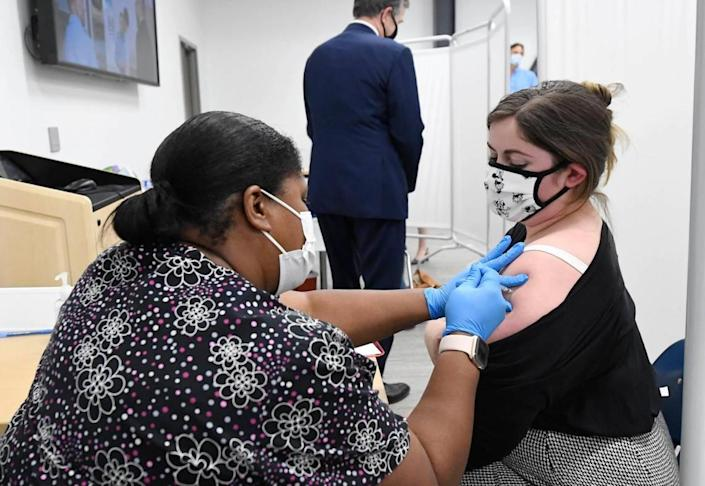 Kendra Gray, left, administers a COVID vaccine to Rachel Willis during a tour by N.C. Gov. Roy Cooper, rear.