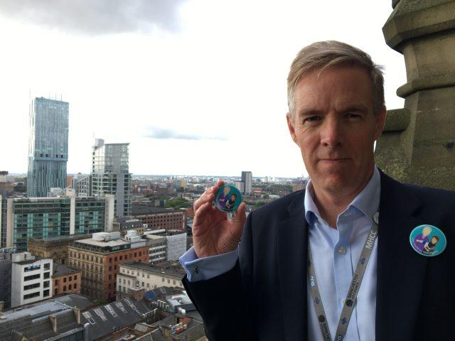 Manchester Health and Care Commissioning chief accountable officer Ian Williamson with the new badge  launched by Girlguides in Manchester to tackle loneliness in old people