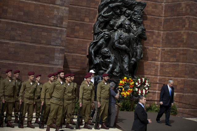 Israeli Prime Minister Benjamin Netanyahu, right, walks after laying a wreath during a ceremony marking the annual Holocaust Remembrance Day at the Yad Vashem Holocaust Memorial in Jerusalem, Monday, April 8, 2013. Israel came to a standstill for two mournful minutes Monday as sirens pierced the air in an annual ritual to remember the 6 million Jews systematically murdered by German Nazis and their collaborators during the Holocaust in World War II. (AP Photo/Oded Balilty)