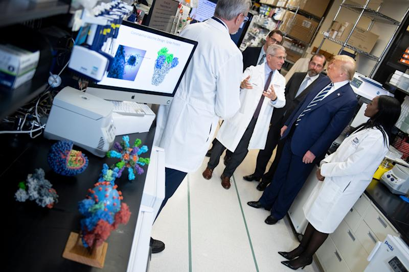 National Institute of Allergy and Infectious Diseases Director Tony Fauci speaks to US President Donald Trump during a tour of the National Institutes of Health's Vaccine Research Center (Getty Images)