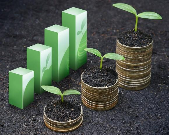 Rising coin stacks with plants growing on top next to a rising bar chart.