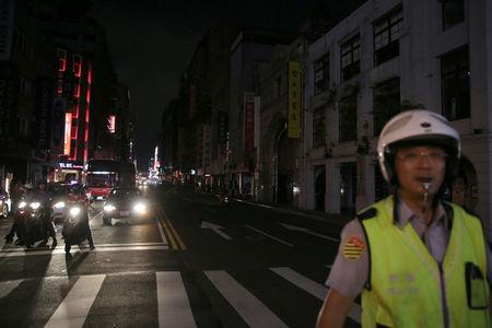 A police stands in front of a building during a massive power outage in Taipei, Taiwan August 15, 2017. REUTERS/Stringer