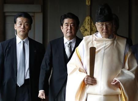 Japan's PM Abe is led by a Shinto priest as he visits Yasukuni shrine in Tokyo