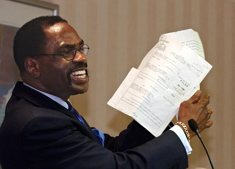 """FILE - In this Jan. 29, 2004 file photo, former boxer, Rubin, """"Hurricane"""" Carter, holds up the writ of habeas corpus that freed him from prison, during a news conference held in Sacramento, Calif. Carter, who spent almost 20 years in jail after twice being convicted of a triple murder he denied committing, died at his home in Toronto, Sunday, April 20, 2014, according to long-time friend and co-accused John Artis. He was 76. (AP Photo/Rich Pedroncelli, File)"""