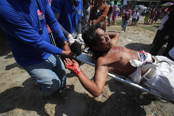A Filipino devotee who was nailed to the cross is carried by medical personnel after blood comes out of his wounds during a re-enactment of the crucifixion of Jesus Christ in San Pedro Cutud village, Pampanga province, northern Philippines on Friday, April 18, 2014. Church leaders and health officials have spoken against the practice which mixes Roman Catholic devotion with folk belief, but the annual rites continue to draw participants and huge crowds. (AP Photo/Aaron Favila)