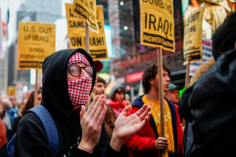 A man covers his face as people take part in an anti-war protest amid increased tensions between the United States and Iran at Times Square in New York