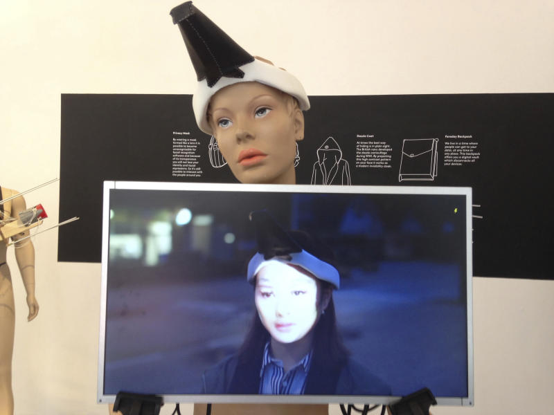 """This 2017 photo provided by artist Jing-cai Liu shows her work titled """"Wearable Face Projector"""" at a gallery in Utrecht, Netherlands. A 2017 video by Liu showing her demonstrating the conceptual art piece, on screen at center, began circulating widely on social media in early October 2019 after Hong Kong instituted an emergency ordinance to ban masks at rallies. Liu said her piece was not intended to be political. She found out that people were sharing her video in relation to the protests when her friends began tagging her in posts with the false caption claiming that protesters in Hong Kong use wearable face projectors to disable the facial recognition system used by the government. (Jing-cai Liu via AP)"""