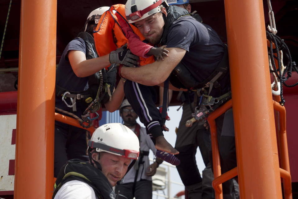 A little girl is carried onto the Ocean Viking humanitarian rescue ship after a rescue operation some 53 nautical miles (98 kilometers) from the coast of Libya in the Mediterranean Sea, Tuesday, Sept. 17, 2019. The humanitarian rescue ship Ocean Viking pulled 48 people from a small overcrowded wooden boat including a newborn and a pregnant woman. (AP Photo/Renata Brito)