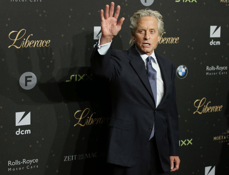 US actor Michael Douglas waves as he arrives for the German premiere of the movie 'Behind The Candelabra' in Berlin, Germany, Monday, Sept. 2, 2013. (AP Photo/Michael Sohn )
