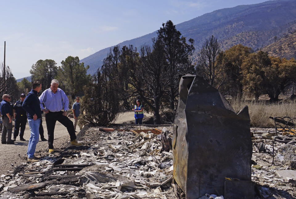 California Gov. Gavin Newsom, left, and Nevada Gov. Steve Sisolak talk as they tour destroyed home by wildfires near where the Tamarack Fire ignited earlier in July in Gardnerville, Nev., Wednesday, July 28, 2021. Nevada Gov. Steve Sisolak and California Gov. Gavin Newsom stood on ashen ground as they surveyed burned homes and a mountain range of pine trees charred by the Tamarack Fire south of Gardnerville, Nevada, near Topaz Lake. The governors, both Democrats, called on the federal government to provide more firefighting resources and stressed that climate change could make wildfires even more intense and destructive in the future. (AP Photo/Sam Metz)