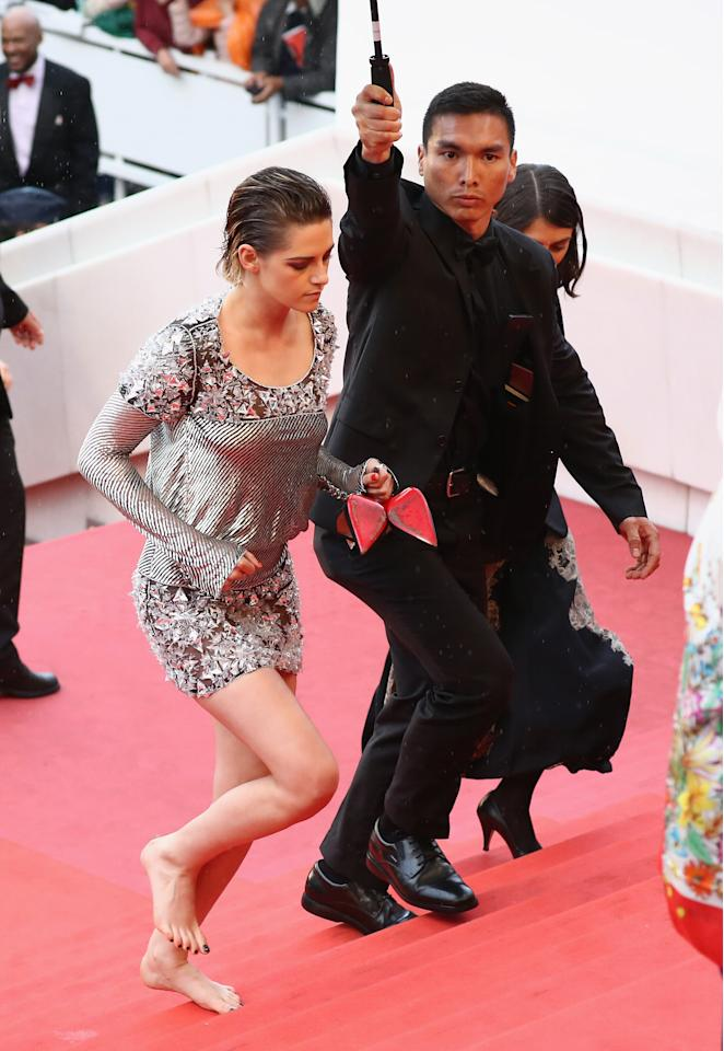 <p>Stewart ran up the famous stairs of the Cannes red carpet while holding her Christian Louboutin stillettos. </p>