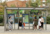 People wearing protective face masks wait at a bus stop at Usera neighbourhood in Madrid