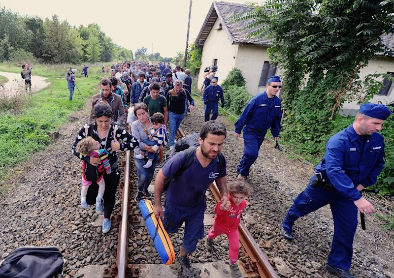 Refugees accompanied by police officers walk on the railway tracks near Szeged town as they broke out from the migrant collection point near Roszke village on September 8, 2015
