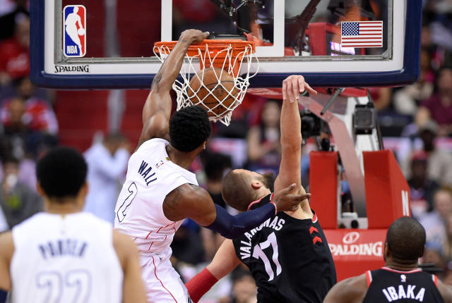 Washington Wizards guard John Wall (2) dunks against Toronto Raptors center Jonas Valanciunas (17) during the first half of Game 4 of an NBA basketball first-round playoff series, Sunday, April 22, 2018, in Washington. (AP Photo/Nick Wass)