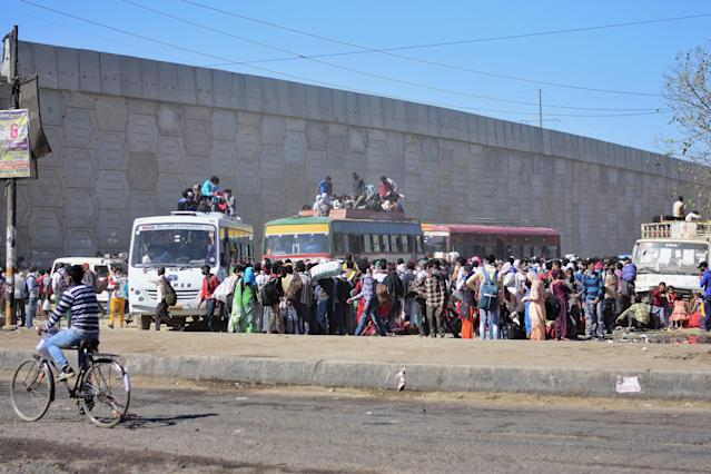 DELHI, INDIA - 2020/03/29: Crowd of migrant workers at Anand vihar bus terminal travelling to their villages, during the nationwide lock down. The Indian government imposed a 21 day nationwide lock down as a preventive measure against the corona virus pandemic. (Photo by Manish rajput/SOPA Images/LightRocket via Getty Images)