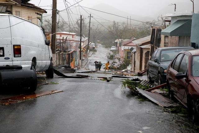 People walk on the street next to debris after the area was hit by Hurricane Maria in Guayama, Puerto Rico September 20, 2017.
