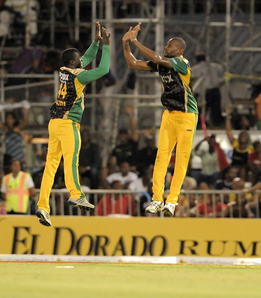 PORT OF SPAIN, TRINIDAD AND TOBAGO - AUGUST 24:  Chadwick Walton (L) and Dave Bernard Jnr. of Jamaica Tallawahs jump in celebration of Guyana Amazon Warriors wicket during the Final of the Caribbean Premier League between Guyana Amazon Warriors v Jamaica Tallawahs at Queens Park Oval on August 24, 2013 in Port of Spain, Trinidad and Tobago. (Photo by Randy Brooks/Getty Images Latin America for CPL)