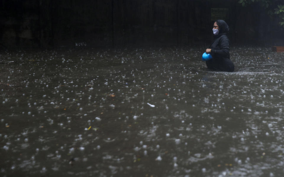 A woman wearing a mask walks through a waterlogged street in Mumbai, India, Monday, May 17, 2021. Cyclone Tauktae, roaring in the Arabian Sea was moving toward India's western coast on Monday as authorities tried to evacuate hundreds of thousands of people and suspended COVID-19 vaccinations in one state. (AP Photo/Rafiq Maqbool)