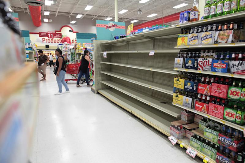 Customers in San Juan walk near empty shelves that are normally filled with bottles of water after Puerto Rico Gov. Ricardo Rossello declared a state of emergency in preparation for Hurricane Irma. (Alvin Baez / Reuters)